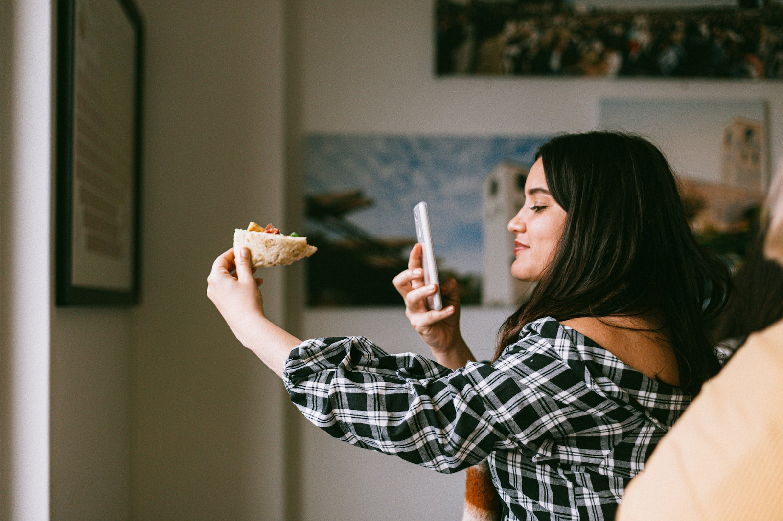 Фотография женщины, фотографирующей кусок пиццы своим телефоном.