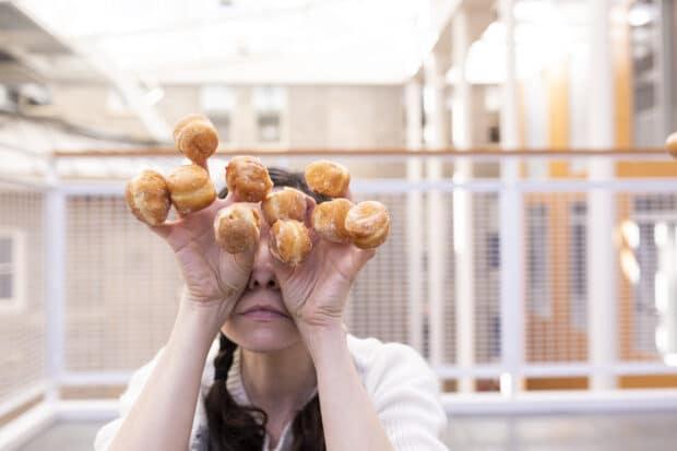 человек, держащий мини-пончики на каждом пальце