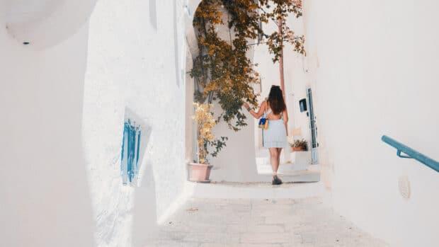 путешественник, идущий по белым улочкам Греции