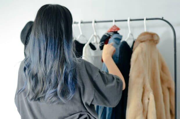 стилист розничной торговли расставляет пальто на вешалках