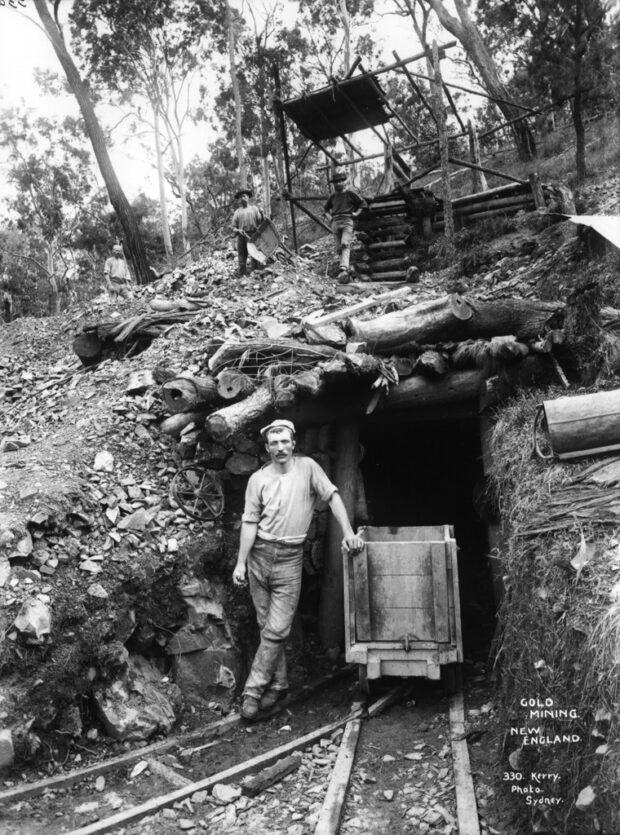 историческое черно-белое изображение человека, стоящего перед золотым рудником Новой Англии