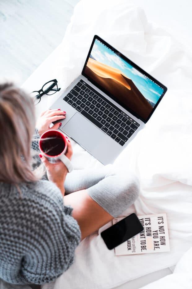 женщина держит чашку кофе и работает за ноутбуком
