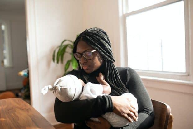 Чернокожая женщина держит новорожденного